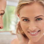Young Woman Smiling Looking in Mirror