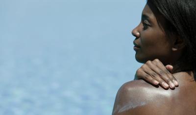 Woman Applying Sunblock on Back