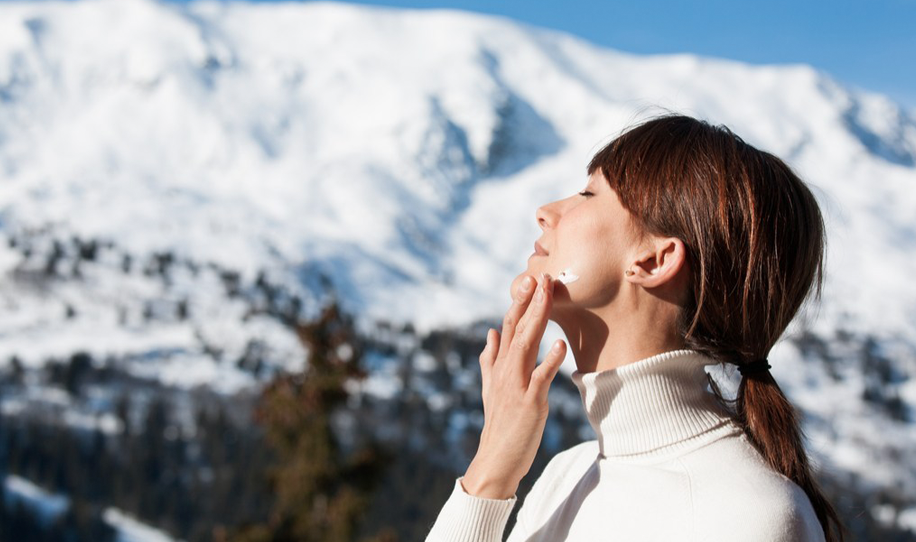 Woman Applying Sunscreen In Front of Snow Mountains